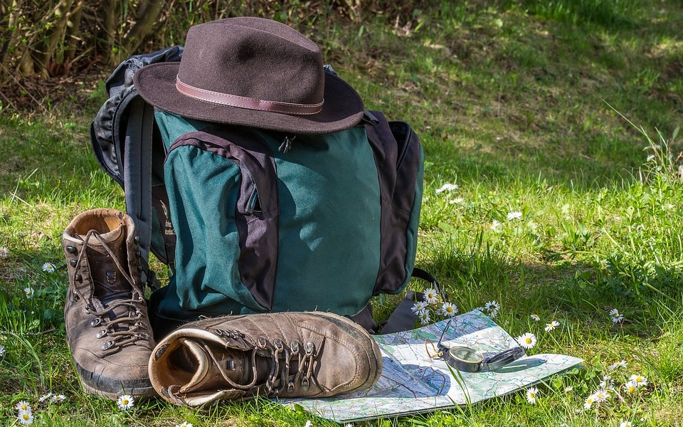 A rucksack, with walking boots and map next to it. A hat lies on top of the hat.