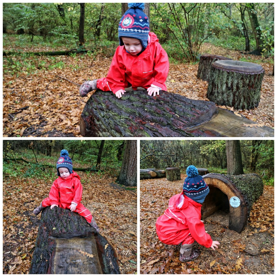 a little boy in hat and full waterproof suit plays on a log