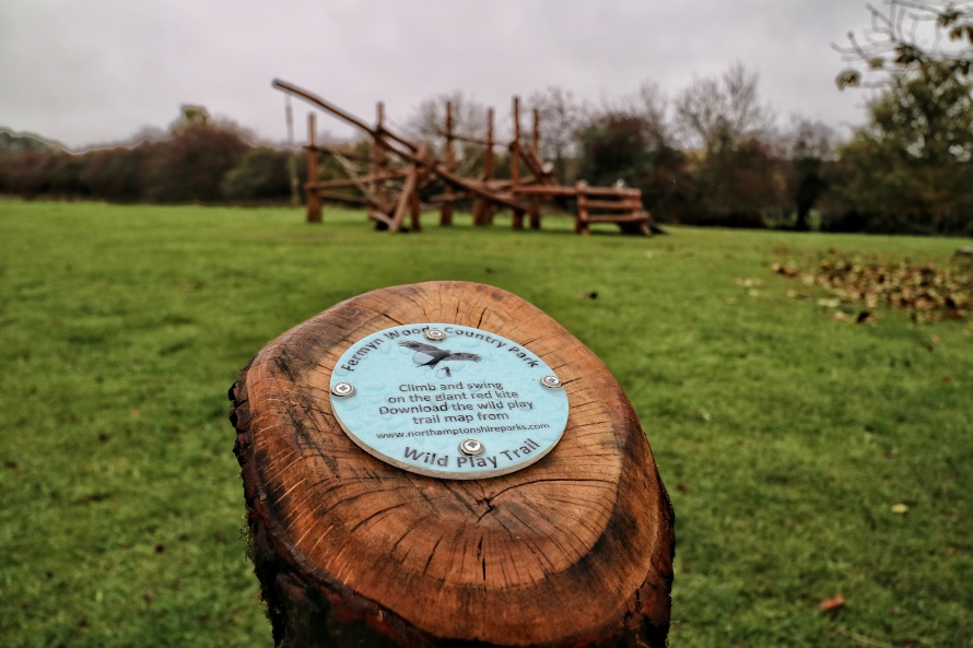 Fermyn Woods wild play trail. Challenge 1 climb and swing on the wooden climbing frame in the background